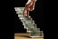 Image of fingers walking up staircase of dollar bills