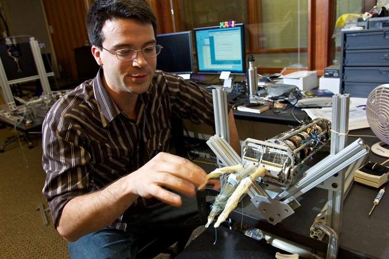 Scientist touches finger of robotic hand