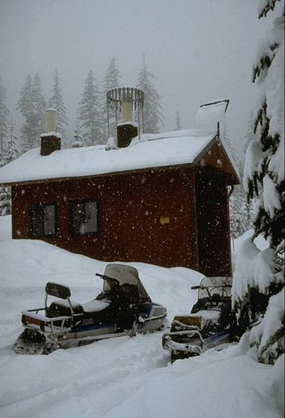 Small red cabin on a snow day, two snowmobiles in front