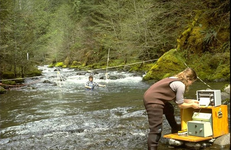 One woman scientist waist-deep in stream, the other looking at a machine readout on the rocky bank