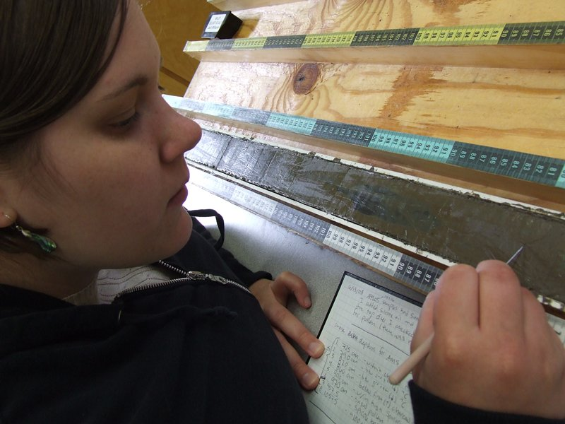 Photo of student researcher examining sediment cores