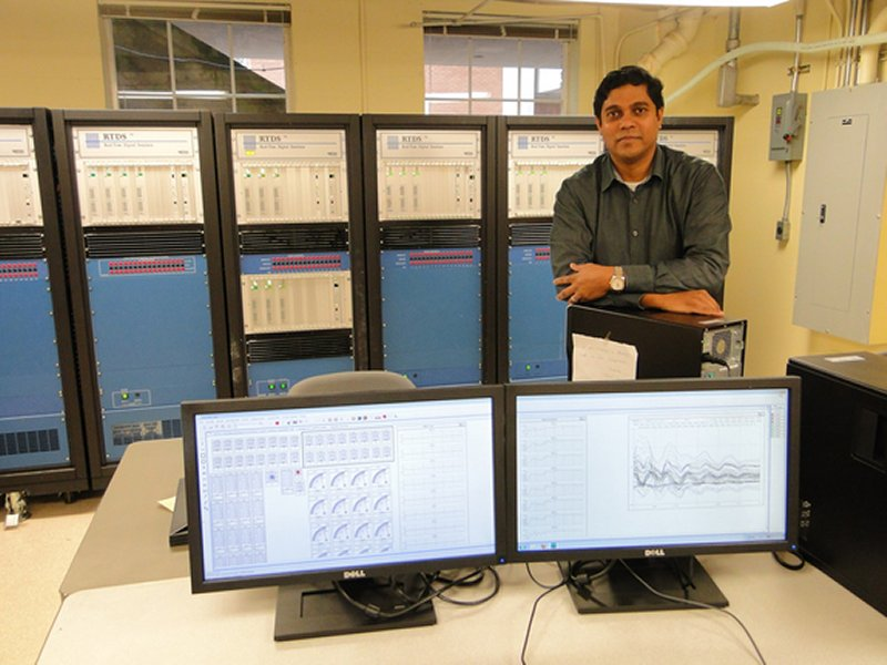 a researcher stands in front of a power system simulator