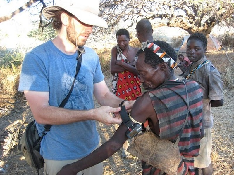 a researcher fits a wearable gps unit on a hadza man