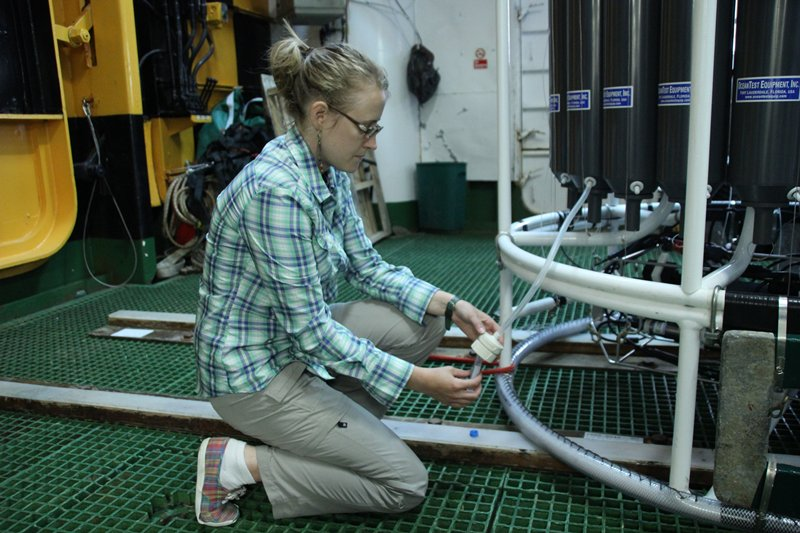graduate student collects seawater samples onboard a research vessel