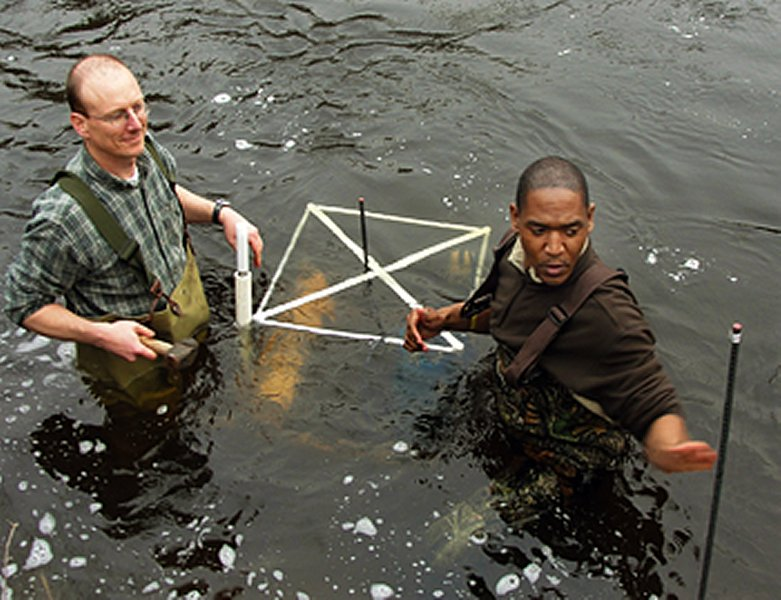 researchers secure an aquatic sensor suite in a river