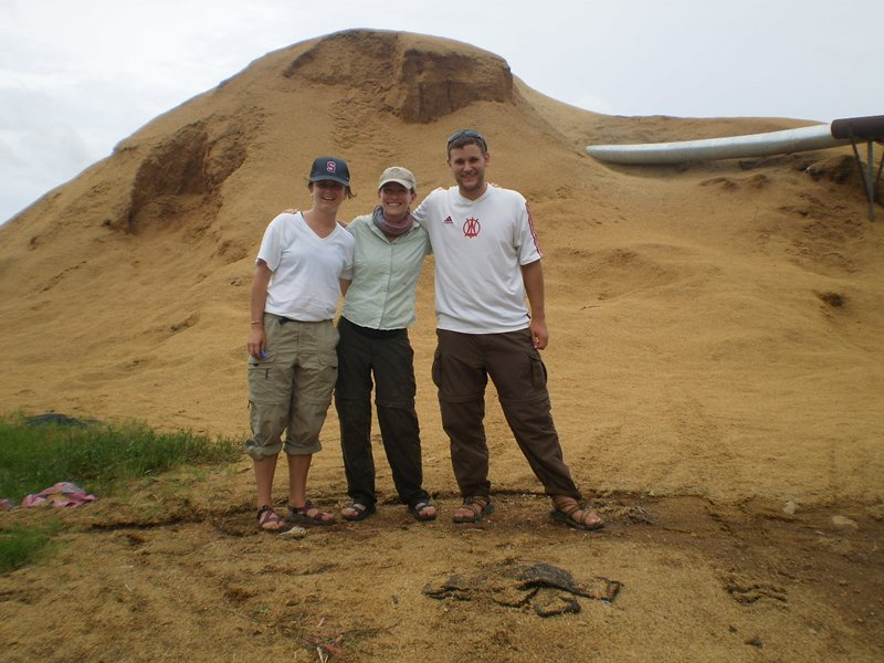 three researchers stand in front of a rice husk pile