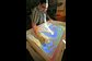 a designer sculpts a waterway in the sand using an augmented-reality sandbox